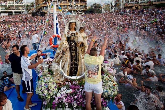 Sailors of the New saint Ramon boat celebrate with the corwd the loading of the Virgen del Carmen statue for its journey on July 15, 2014 at Puerto de la Cruz dock on the Canary island of Tenerife, Spain. (Photo by Gonzalo Arroyo Moreno/Getty Images)