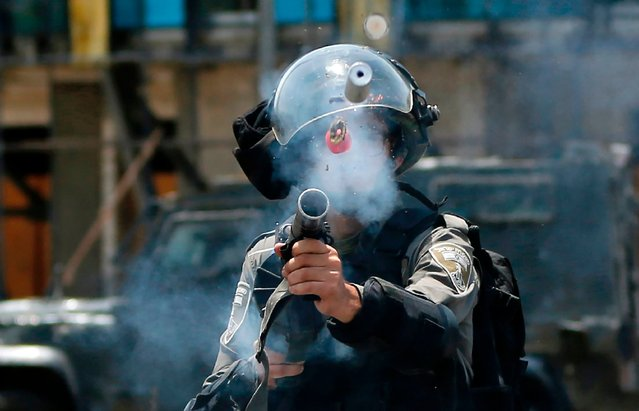 An Israeli border guard fires a tear gas canister towards Palestinian protesters during clashes near the Jewish settlement of Beit El, near the West Bank city of Ramallah, on July 24, 2017, following a demonstration against new Israeli security measures implemented at the holy site following an attack that killed two Israeli policemen the previous week Israel installed metal detectors at entrances to the site following an attack nearby on July 14 that killed two of its policemen. Palestinians view the move as Israel asserting further control over the compound, home to Al- Aqsa mosque and Dome of the Rock, and considered Islam' s third holiest site. (Photo by Abbas Momani/AFP Photo)