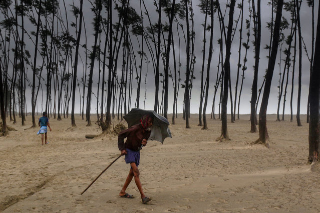 A Bangladeshi villager evacuates to a cyclone shelter on the coast in Cox's Bazar district on May 30, 2017. Cyclone Mora hit Bangladesh on May 30, packing winds of up to 135 kilometres (84 miles) per hour, damaging thousands of homes as more than 300,000 people fled coastal villages. (Photo by AFP Photo/Stringer)