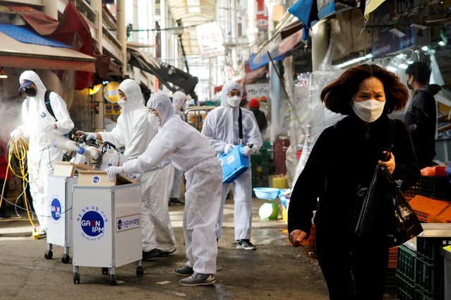 A woman wearing a mask to prevent contracting the coronavirus reacts as employees from a disinfection service company sanitize a traditional market in Seoul, South Korea, February 26, 2020. (Photo by Kim Hong-Ji/Reuters)