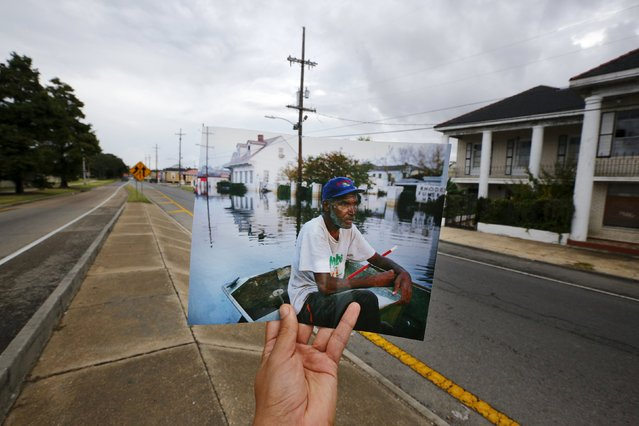 Photographer Carlos Barria holds a print of a photograph he took in 2005, as he matches it up at the same location 10 years on, in New Orleans, United States, August 16, 2015. The print shows Errol Morning sitting on his boat on a flooded street September 5, 2005, after Hurricane Katrina struck. (Photo by Carlos Barria/Reuters)