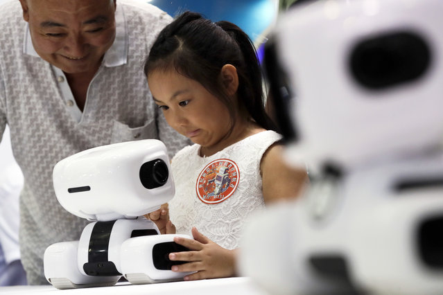 A child reacts as she tries out a robotic Padbot T2 at an exhibitor booth during the World Robot Conference at the Yichuang International Conference and Exhibition Centre in Beijing, Wednesday, August 23, 2017. The annual conference is a showcase of China's burgeoning robot industry ranging from companion robots to those deployed on manufacturing assembly line and entertainment. (Photo by Andy Wong/AP Photo)