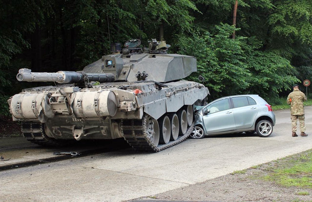 "A handout photo provided by the Police department in Lippe on 01 June 2015 of a British ""Challenger 2"" tank after it rolled over a car's front in Lippe, Germany, 01 June 2015. Police reported that a 18-year old female driving beginner from Detmold apparently overlooked a convoy of tanks when she turned left onto the Panzeringstrasse (lit. Tank Ring Road). The driver of the convoy'e leading tank, a 24-year old British national, was not able to stop his vehicle fast enough, hit the car and overran the vehicle's front. The young female car driver remained unhurt. The exclusive damage to the car was estimated at about 12,000 euro. (Photo by EPA/Polizei Lippe)"