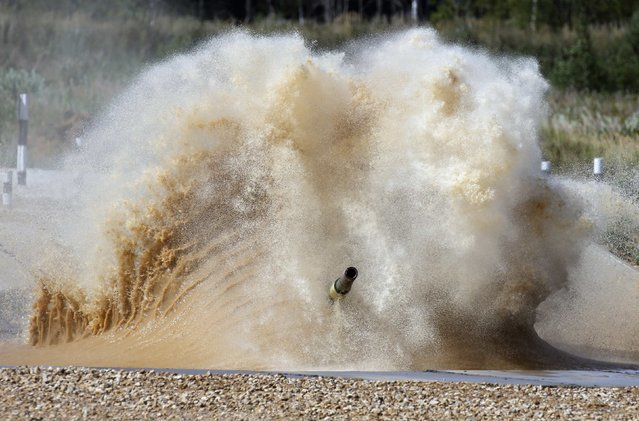 A tank drives through a water obstacle on the course of the Tank Biathlon world championship in Alabino outside Moscow August 4, 2014. The tank competition, where teams compete in tests of driving and shooting, will for the first time bring together crews from 12 countries: Angola, Armenia, Belarus, Venezuela, India, Kazakhstan, Kyrgyzstan, China, Kuwait, Mongolia, Russia and Serbia, local media reported. (Photo by Maxim Shemetov/Reuters)