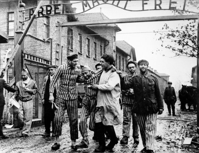 "A doctor (centre) of the 322nd Rifle Division of the Red Army, with a group of survivors at the entrance to the newly-liberated Auschwitz I concentration camp, Poland, January 1945. The Red Army liberated the camp on 27th January 1945. Above the gate is the motto ""Arbeit macht frei"" (""Work brings freedom""). (Photo by Fine Art Images/Heritage Images/Getty Images)"