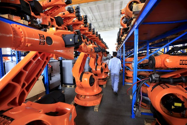A worker walks past second-hand robots in a factory in Shanghai, August 21, 2015. More than a hundred second-hand robots used to make Audi A3s at a German car factory are going through refurbishment at a Wecan Group factory in Shanghai. Picture taken August 21, 2015. (Photo by Aly Song/Reuters)