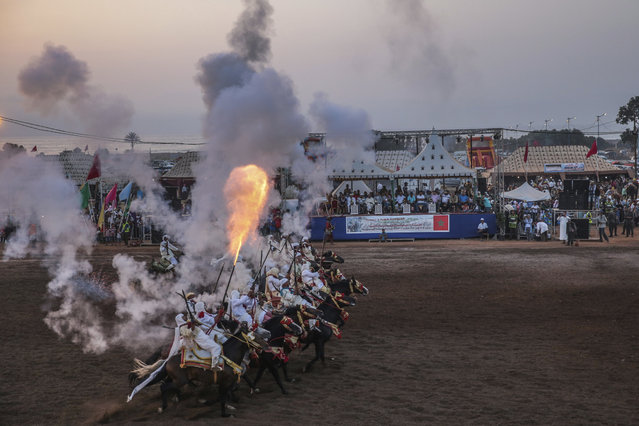 In this Thursday, August 17, 2017 photo, a troupe charges and fire their rifles during Tabourida, a traditional horse riding show also known as Fantasia, in Mansouria, near Casablanca, Morocco. (Photo by Mosa'ab Elshamy/AP Photo)