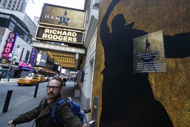 Theatre personnel leave the Richard Rodgers theatre that is closed due to COVID-19 concerns in Times Square, Thursday, March 12, 2020, in New York. New York City Mayor Bill de Blasio said Thursday he will announce new restrictions on gatherings to halt the spread of the new coronavirus in the coming days. For most people, the new coronavirus causes only mild or moderate symptoms. For some it can cause more severe illness. (Photo by John Minchillo/AP Photo)