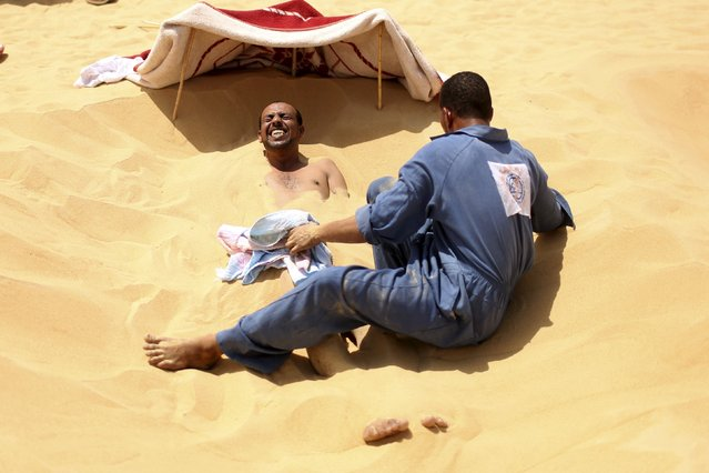 A patient grimaces as a worker covers his body in hot sand in Siwa, Egypt, August 11, 2015. (Photo by Asmaa Waguih/Reuters)