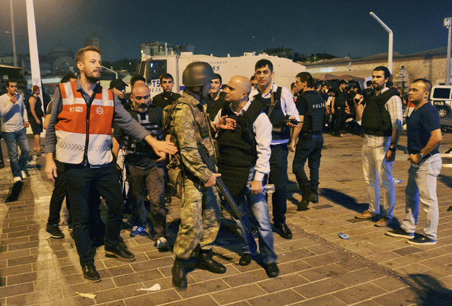 A Turkish police officer, center right, confronts a Turkish army officer, center left, that participated in the coup, after he was apprehended by civilians and handed over, in Istanbul's Taksim square, early Saturday, July 16, 2016. (Photo by Selcuk Samiloglu/AP Photo)