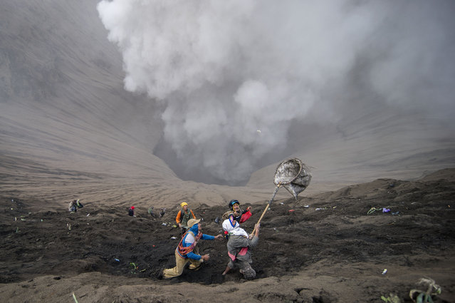 Villagers catch coin offerings released by Hindu devotees of the Tengger tribe during the Yadnya Kasada festival, on the crater of Mount Bromo in Probolinggo on July 21, 2016. (Photo by Juni Kriswanto/AFP Photo)