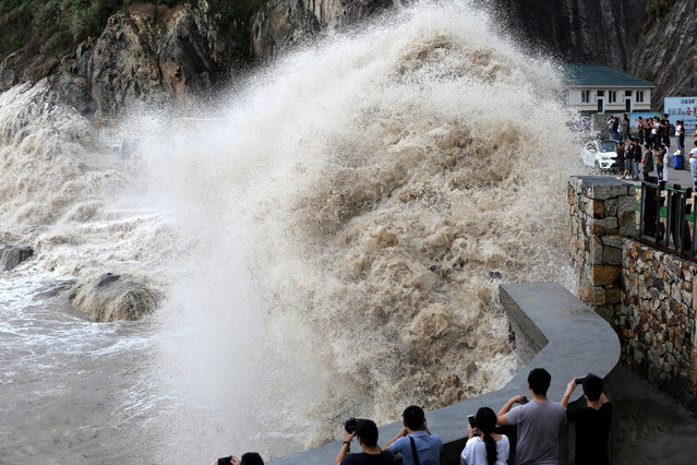 People stand beside a big wave on a waterfront as Typhoon Talim approaches in Wenling, Zhejiang province, China September 14, 2017. (Photo by Reuters/China Stringer Network)
