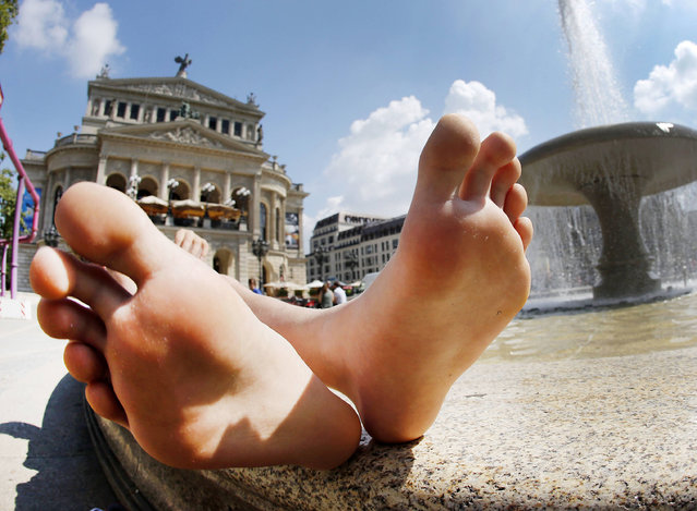 A young man rests at a fountain in front of the Old Opera in Frankfurt, Germany on a warm Wednesday, July 27, 2016. (Photo by Michael Probst/AP Photo)