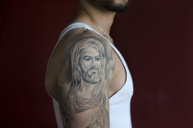 In this Tuesday, May 31, 2016 photo, Ali, 22, poses for a photo showing off his tattoo of Shiite Muslims' first Imam Ali, in the southern suburb of Beirut, Lebanon. (Photo by Hassan Ammar/AP Photo)