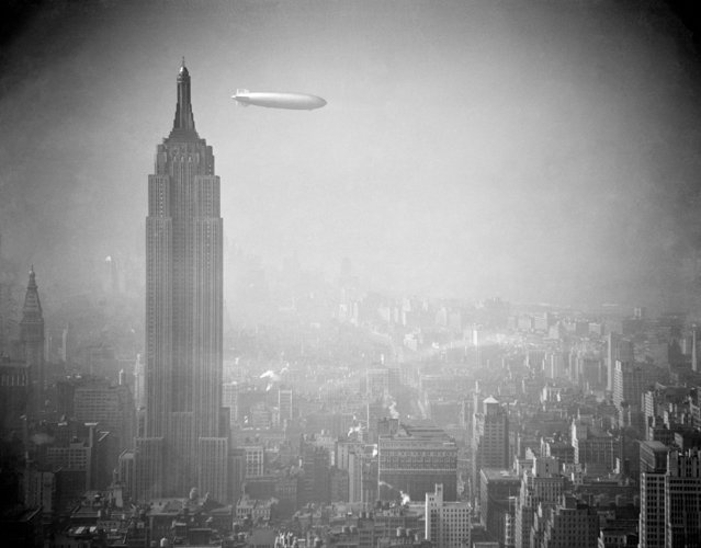 The Zeppelin Hindenburg floats in a hazy sky near the Empire State Building over Manhattan, August 8, 1938. The German airship is en route to Lakehurst, N.J. from Germany. (Photo by AP Photo)