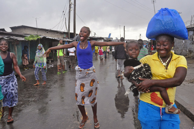 A woman, center,  reacts as she and others celebrate on the streets outside of West Point, that have been closed in by Liberian security forces to stop all movement the past week in a attempt to control the Ebola outbreak in Monrovia, Liberia, Saturday, August 30, 2014. Liberia says it will open up a slum in its capital where thousands of people were barricaded to contain the spread of Ebola. Information Minister Lewis Brown says lifting the quarantine Saturday morning will not mean there is no Ebola in the West Point Slum. (Photo by Abbas Dulleh/AP Photo)