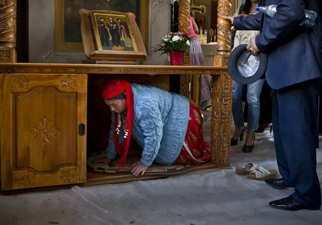 A Romanian Roma woman passes under a table, part of a local tradition, during a religious service celebrating the Birth of the Virgin Mary at the Bistrita Monastery in Costesti, Romania, Monday, September 8, 2014. (Photo by Vadim Ghirda/AP Photo)