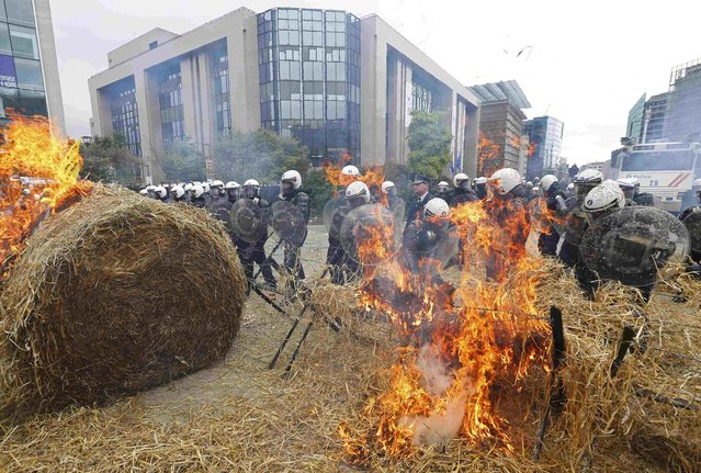 Belgian riot police officers stand guard while demonstrators burn hay as farmers and dairy farmers from all over Europe take part in a demonstration outside an European Union farm ministers emergency meeting at the EU Council headquarters in Brussels, Belgium, September 7, 2015. (Photo by Yves Herman/Reuters)