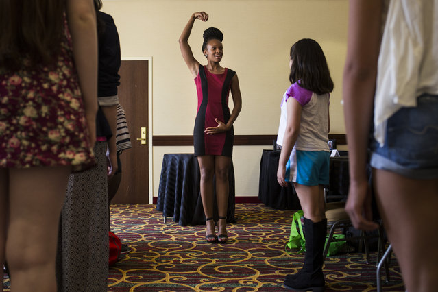 Rogi Banks, 25, of Washington, DC, speaks to camp attendees about posture while illustrating a technique at a modeling camp at the Courtyard Marriott Hotel in McLean, Va., on Monday, August 17th, 2015. (Photo by Brittany Greeson/The Washington Post)