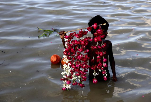 A boy waits to sell rose petals to Hindu pilgrims standing on the bank of the holy Sangam, confluence of Ganges river, Yamuna river and mythical saraswati river in Allahabad, India , Thursday, August 4, 2016. (Photo by Rajesh Kumar Singh/AP Photo)