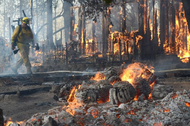 In this Sunday, September 14, 2014 photo, a firefighter walks past a burning structure on Cedar Drive in Oakhurst, Calif., as two raging wildfires in the state forced hundreds of people to evacuate their homes. (Photo by Mark Crosse/AP Photo/The Fresno Bee)