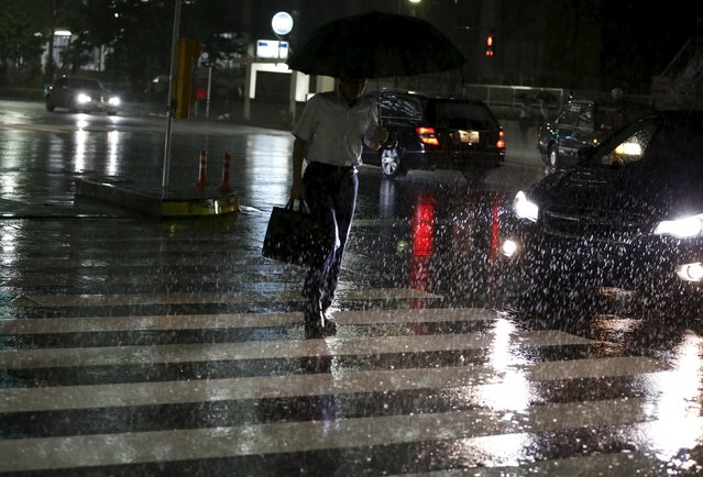 A businessman holding an umbrella walks as heavy rain caused by typhoon Etau falls in Tokyo's business district September 9, 2015. Typhoon Etau made landfall in central Japan on Wednesday morning, bringing strong winds and heavy rains as authorities warned of possible landslides and flooding, local media reported. (Photo by Issei Kato/Reuters)