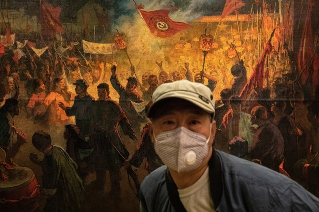 "A man wearing a protective face mask walks past a painting as he visits ""A tribute to donors"" exhibition at the National Art Museum of China on the first day after reopening, in Beijing, China, 13 May 2020. The National Art Museum of China was reopened for visitors for the first time after it was closed down in January due to the outbreak of the coronavirus and COVID-19 disease. (Photo by Roman Pilipey/EPA/EFE)"