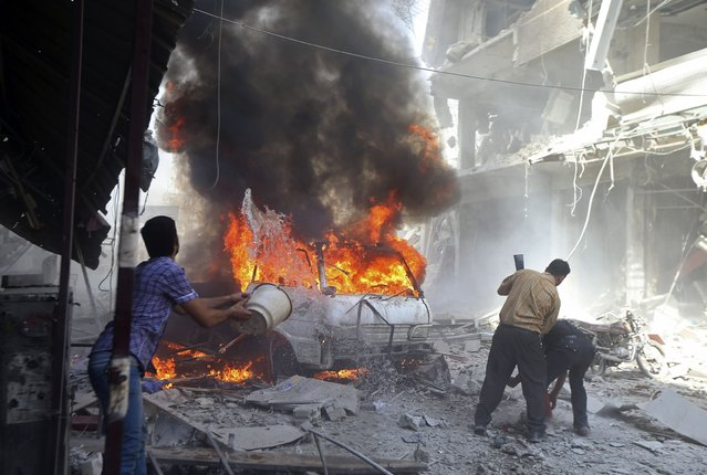 Residents try to put out a fire at a site after what activists said were two air strikes by forces of Syria's President Bashar al-Assad on a market in central Douma, eastern al-Ghouta, near Damascus September 17, 2014. (Photo by Bassam Khabieh/Reuters)
