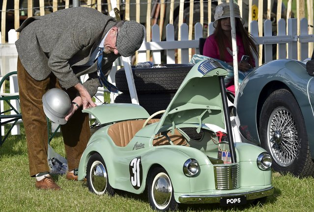 A man examines a a children's pedal car at the Goodwood Revival historic motor racing festival in Goodwood, near Chichester in south England, Britain, September 11, 2015. (Photo by Toby Melville/Reuters)