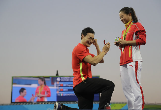 China's diver Qin Kai, left, cheers after silver medalist He Zhi of the women's 3-meter springboard diving finals accepted his marriage proposal in the Maria Lenk Aquatic Center at the 2016 Summer Olympics in Rio de Janeiro, Brazil, Sunday, August 14, 2016. (Photo by Wong Maye-E/AP Photo)