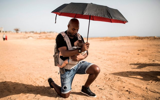 Alexis kneels with his baby at a protest in solidarity with the Black Lives Matter movement in Dakar, Senegal on June 9, 2020. (Photo by John Wessels/AFP Photo)