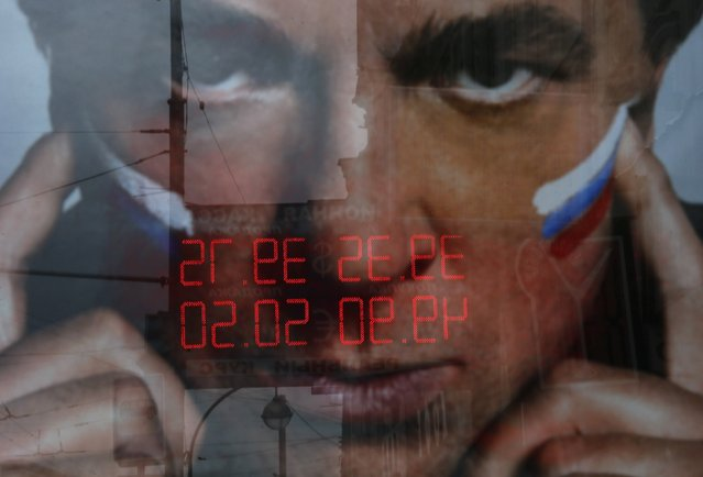 A board displaying currency exchange rates is reflected in an advertising panel in Moscow, September 29, 2014. The Russian rouble reached a new historic low against the dollar and the currency basket on Monday because of the demand for the American currency, both external and internal, as well as on the back of low oil prices. (Photo by Maxim Shemetov/Reuters)