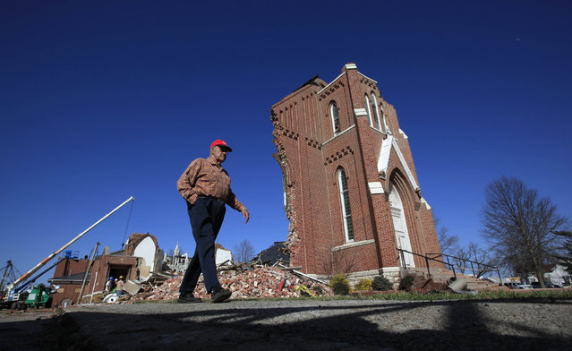 A man walks by the destroyed St. Joseph's Catholic Church which was damaged by a tornado in Ridgway, Illinois, March 1, 2012. (Photo by Jim Young/Reuters)