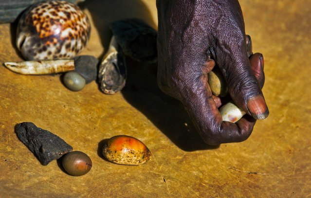 Kenyan witch-doctor John Dimo, who claims to be 105 years old, throws shells, bones, and other magic items to predict the outcome of the presidential election, in front of his hut in the village of Kogelo, where President Barack Obama's late father came from and whom Dimo claims to have known, in western Kenya, November 5, 2012. He said Obama will win. (Photo by Ben Curtis/Associated Press)