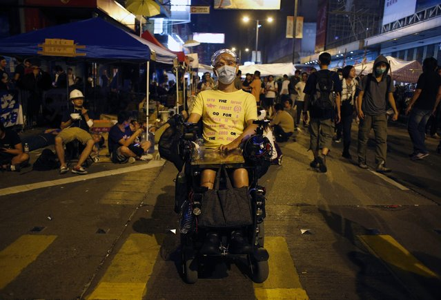 "Young, 49, poses on Nathan Road at Mongkok shopping district in Hong Kong October 6, 2014. Wearing goggles and a face mask, Young said, ""I come here not supporting students but support the spirit of this movement"". (Photo by Bobby Yip/Reuters)"