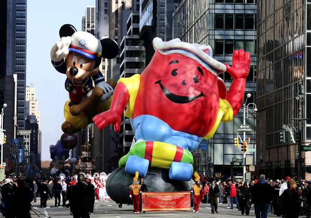 The Kool-Aid Man balloon and the Mickey Mouse balloon participate in the 86th annual Macy's Thanksgiving Day Parade in New York. (Photo by Librado Romero/The New York Times)