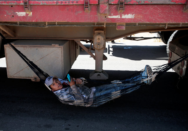 A truck driver rests during the road blockade by independent miners protesting against Bolivia's President Evo Morales' government policies near Panduro south of La Paz, Bolivia, August 25, 2016. (Photo by David Mercado/Reuters)