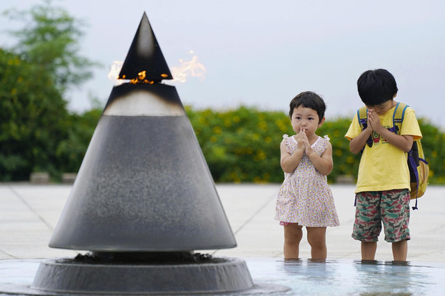 """Children pray in front of the """"Peace of Fire"""" at the Peace Memorial Park in Itoman, Okinawa, Japan, Tuesday, June 23, 2020. Okinawan people find it unacceptable that their land is still occupied by a heavy U.S. military presence even 75 years after World War II. They have asked the central government to do more to reduce their burden, and Japanese Prime Minister Shinzo Abe's government repeatedly say it is mindful of their feelings, but the changes are slow to come. (Photo by Koji Harada/Kyodo News via AP Photo)"""
