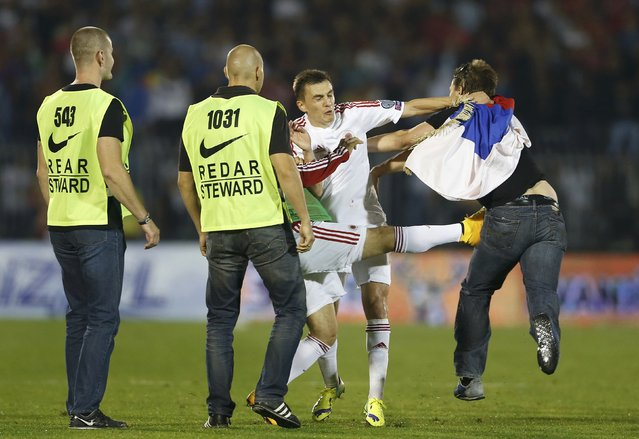 Albania's Burim Kukeli (C) and a teammate clash with fan of Serbia during their Euro 2016 Group I qualifying soccer match at the FK Partizan stadium in Belgrade October 14, 2014. (Photo by Marko Djurica/Reuters)