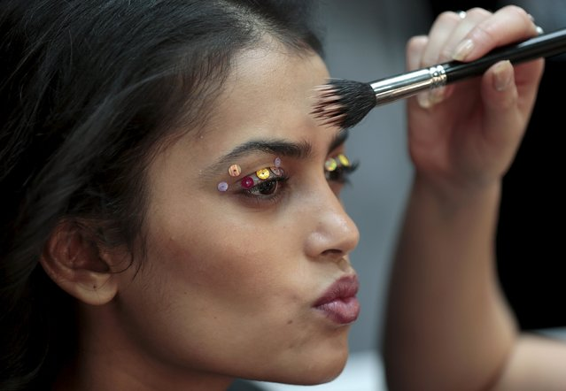 A model has her makeup done backstage before the presentation of the Ashish Spring/Summer 2016 collection during London Fashion Week in London, Britain September 22, 2015. (Photo by Suzanne Plunkett/Reuters)