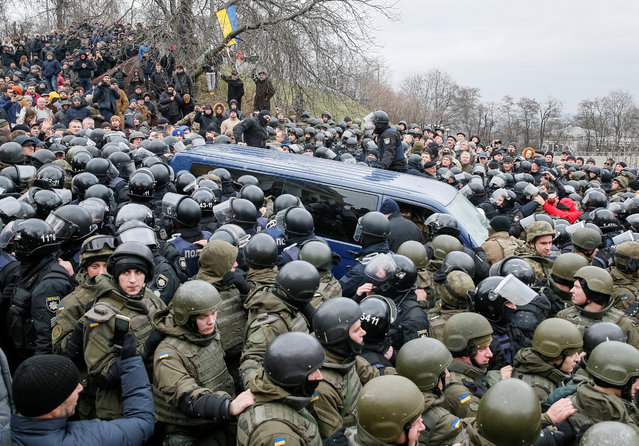 Ukrainian National Guard officers guard a car carrying former Georgian President Mikheil Saakashvili during clashes with his supporters in Kiev, Ukraine, Tuesday, December 5, 2017. Masked officers had earlier dragged Saakashvili, 49, from an apartment in the Ukrainian capital. But his supporters prevented the police van from moving off, hemming it in and eventually freeing him by breaking its windows and back door. (Photo by Gleb Garanich/Reuters)