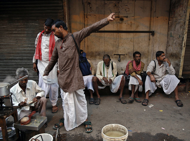 Men sit in front of closed shops as they wait to have their morning tea from a roadside vendor in the old quarters of Delhi, October 17, 2014. (Photo by Ahmad Masood/Reuters)