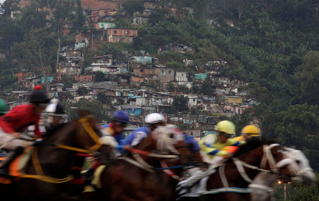 """Competitors take part in a horserace, with a slum or """"barrio"""" in the background at La Rinconada Hippodrome, Caracas, Venezuela, October 8, 2017. (Photo by Ricardo Moraes/Reuters)"""