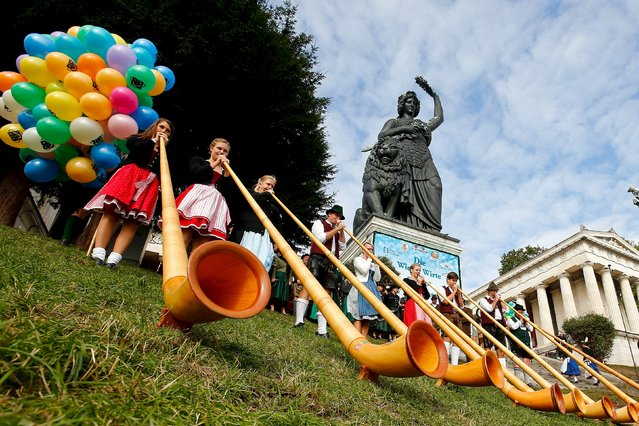 A Alphorn band in traditional Bavarian clothes play instruments during the traditional concert at the 182nd Oktoberfest in Munich September 27, 2015. Millions of beer drinkers from around the world will come to the Bavarian capital for the Oktoberfest, which runs until October 4, 2015. (Photo by Michael Dalder/Reuters)