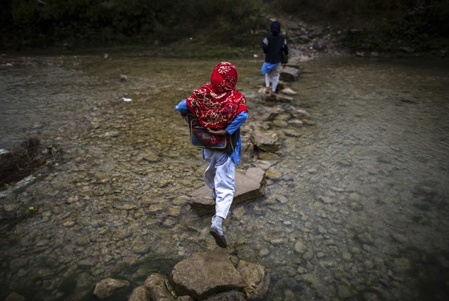 A girl crosses a stream as she walks to school in Margalla Hills, Islamabad, October 24, 2014. (Photo by Zohra Bensemra/Reuters)
