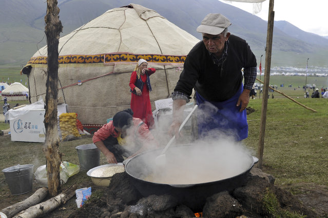 In this photo taken on Sunday, September 4, 2016, a family cooks traditional food during the second World Nomad Games at Issyk Kul lake in Cholpon-Ata, Kyrgyzstan. (Photo by Vladimir Voronin/AP Photo)