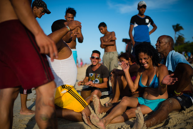 A group of Cubans use tin cans, sticks and their voices to make amazing music on the shore of Santa Maria beach, about 15 miles from Havana. It is the closest beach to Havana. The government is demolishing buildings all over the coast of East Havana and recovering and restoring beach dunes. (Photo by Sarah L. Voisin/The Washington Post)