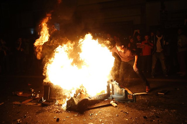 A reveller reaches into the fire that was started in celebration in San Francisco, California October 29, 2014. (Photo by Stephen Lam/Reuters)