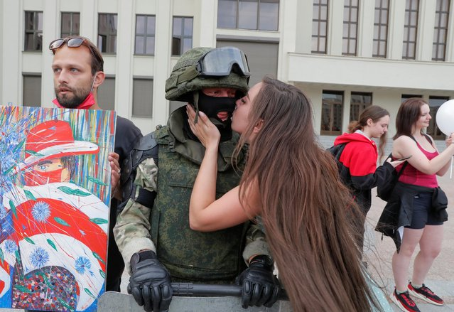 A participant kisses a member of Belarusian Interior Ministry troops, who stands guard during an opposition demonstration to protest against police violence and to reject the presidential election results near the Government House in Independence Square in Minsk, Belarus on August 14, 2020. (Photo by Vasily Fedosenko/Reuters)