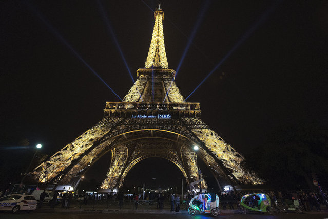 The lettering 'Fashion loves Paris' is projected onto the Eiffel Tower during the Paris Fashion Week Spring/Summer 2016 Ready to Wear collection, in Paris, France, 04 October 2015. The presentation of the Women's collections runs from 29 September to 07 October. (Photo by Caroline Blumberg/EPA)
